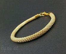 Złota bransoletka wykonana z milimetrowych, galwanizowanych koralików.