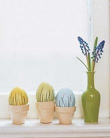 Pastelowe jajka ozdobione źdźbłami trawy. Wyglądają bardzo elegancko.