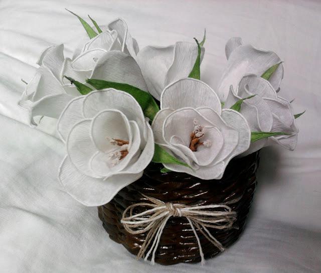 Kwiaty z bibuły w koszyku z papierowej wikliny.