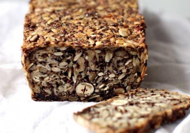 Domowy chleb (bez mąki) Jeśli (podobnie jak my) jesteś wiecznie na diecie i masz wyrzuty sumienia jedząc biały chleb, pokochasz ten przepis! Chleb zrobiony bez mąki, za to z najzdrowszymi orzechami, nasionami i zbożami, które dostarczają mnóstwo błonnika i potrzebnych mikroelementów. Potrzebujesz: 1 szklankę ziaren słonecznika, 1/2 szklanki siemienia lnianego, 1/2 szklankę orzechów laskowych lub migdałów, 1 1/2 szklanki płatków owsianych górskich, 2 łyżki nasion chia (szałwia hiszpańska, do kupienia w eko-sklepach), 4 łyżki nasion babki płesznika, 1 łyżeczka drobnej soli morskiej, 1 łyżka syropu klonowego, 3 łyżki masła klarowanego, 350 ml wody 1. W elastycznej, silikonowej formie wymieszaj wszystkie suche składniki. Syrop klonowy, masło i wodę wymieszaj w kubku. Dodawaj stopniowo do suchych składników mieszając dokładnie. Ciasto powinno być bardzo gęste. Wyrównaj wierzch. Odstaw na minimum 2 godziny a najlepiej na całą noc. Ciasto jest gotowe, gdy utrzymuje kształt po odsunięciu ścianek foremki. 2. Rozgrzej piekarnik do 180 st. C. 3. Piecz chleb przez 20 minut na środkowej półce w piekarniku. Następnie wyjmij z formy, umieść do góry dnem na kratce i piecz przez 30-40 minut. Chleb jest gotowy, gdy popukany od spodu wydaje głuchy dźwięk. 4. Przechowuj w szczelnie zamkniętym pojemniku.