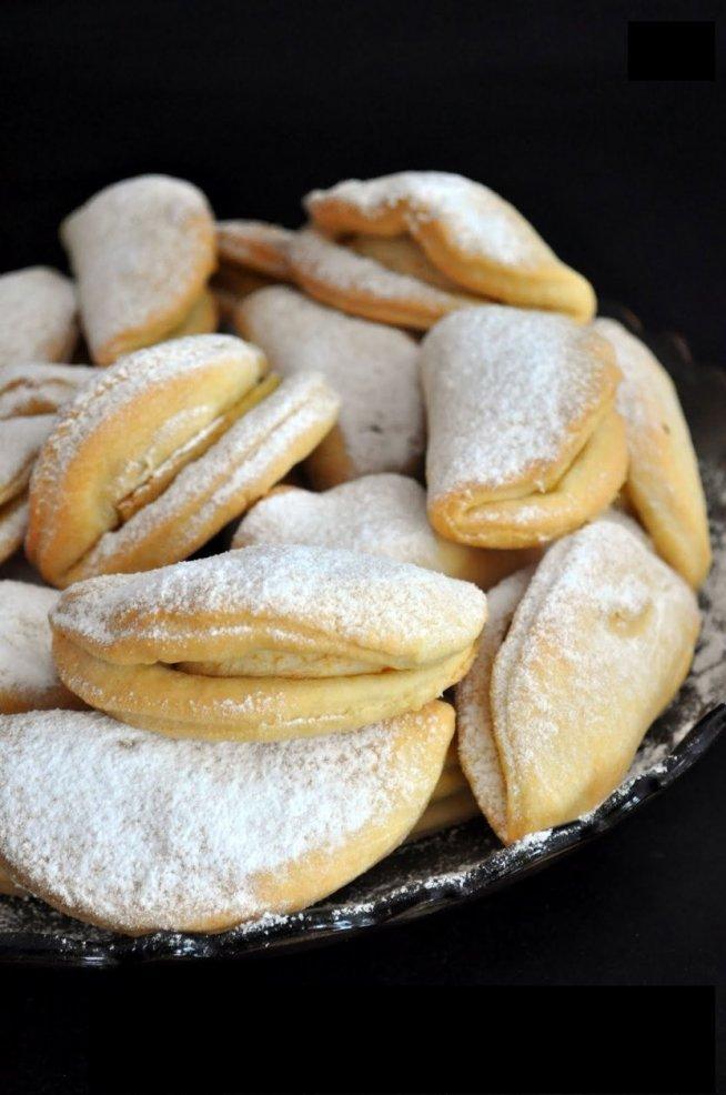 CIASTECZKA DROZDZOWE Z JABLKIEM.  Składniki na ok. 30 szt:  350g mąki  200g masła  10g świeżych drożdży  1/2 łyżki cukru  100g kwaśnej śmietany (18%)  1 jajko+1 żółtko  szczypta soli  jabłka (ok. 3-4 szt)  Drożdże wkruszyć do miseczki i zasypać cukrem. Poczekać aż się rozpuszczą. W misce mąkę posiekać z masłem. Dodać drożdże i resztę składników. Dokładnie wyrobić ciasto. Przykryć folią i wstawić do lodówki na całą noc. Następnego dnia ciasto rozwałkować na grubość ok. 3 mm i wycinać koła o wielkości ok. 10cm. Jabłka pokroić na ósemki lub szesnastki w zależności od wielkości jabłka i wkładać na koło.Sklejać jak pierogi z tym, że tylko boki. Środek ma zostać niesklejony. Piec w 180 stopniach ok.15-20 min. (na złoty kolor). Gdy ostygną posypać obficie pudrem.
