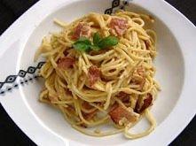 Składniki:  500g makaronu spaghetti 200g szynki szwarcwaldzkiej 250ml śmietanki 30% 3 żółtka ząbek czosnku świeżo mielony pieprz 3 łyżki startego parmezanu 1 cebula 100ml białeg...