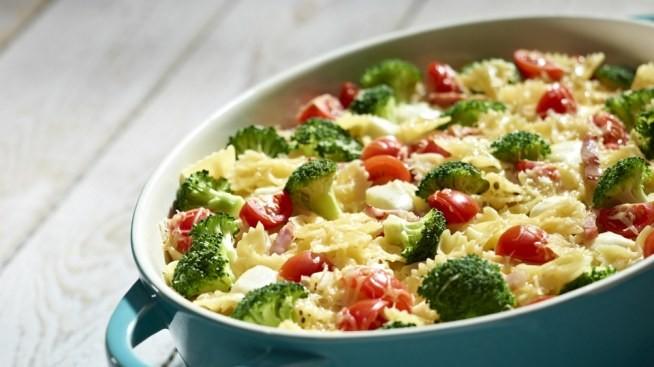 Co kupić suchy makaron kokardki: 300 g średnia cebula: 1 szt. brokuł, umyty: 1 szt. jajka: 2 szt. boczek parzony: 1 opakowanie małe pomidory: 175 g śmietanka 30%, słodka: 200 g mozzarella: 1 szt. ser Gran Padano, starty na małych oczkach: 40 g sól: do smaku pieprz: do smaku  Przygotowanie Cebulę siekamy bardzo drobno w kosteczkę. Całe opakowanie boczku kroimy w paski. 300 g suchego makaronu gotujemy w osolonej wodzie. Małym nożem wycinamy różyczki brokułu, następnie kroimy je na mniejsze kawałki. Do garnka z wrzącą, osoloną wodą wrzucamy różyczki brokułu i gotujemy bez przykrycia. Na patelnię (bez tłuszczu) dodajemy boczek, smażymy, mieszamy. Do boczku na patelni dodajemy cebulę, całość mieszamy. Do kolejnej miski wlewamy śmietankę, wbijamy 2 całe jajka, mieszamy, następnie dodajemy sól i pieprz. Małe pomidory kroimy w ćwiartki. Wyciągamy z wody ugotowane brokuły. Ugotowany i odcedzony makaron wkładamy do naczynia żaroodpornego, zalewamy śmietaną, dodajemy pomidory, boczek i cebulę z patelni i odcedzone brokuły. Mozzarellę kroimy na kosteczkę, dodajemy do zapiekanki. Wszystkie składniki dokładnie mieszamy, doprawiamy solą i pieprzem. Na sam wierzch ścieramy 40 g grana padano. Wkładamy do piekarnika (najpierw pieczemy ok. 10 minut w 180°C (termoobieg), następnie około 5-10 minut w 200 stopniach C (funkcja grill). Wyciągamy zapiekankę z pieca.