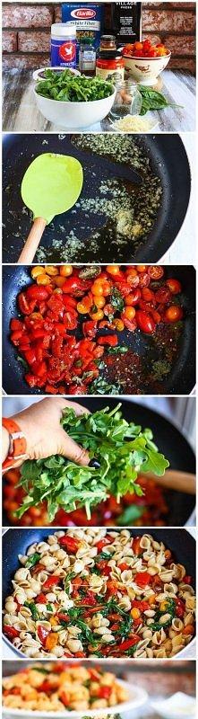 Makaron z pomidorami i rukolą 30 dag makaronu 2 łyżeczki oliwy z oliwek  1 cebula, pokrojona 1 ząbek czosnku, wycisnąć przez praskę  2 szklanki  pomidorów koktajlowych ½ szklank...