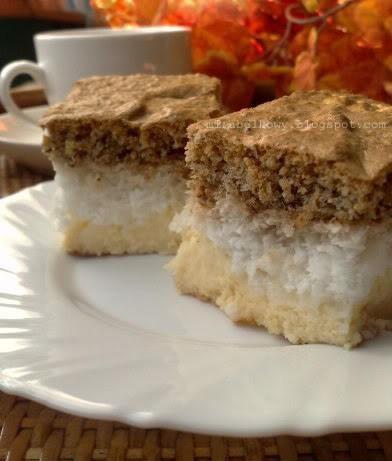 CIASTO SEROWO-KOKOSOWO-ORZECHOWE ciasto serowe: 600g mielonego twarogu, 120g masła, 250g cukru pudru, 6 jajek (oddzielone żółtka od białek), 2 łyżki mąki ziemniaczanej, ½ łyżeczki proszku do pieczenia kilka kropli aromatu waniliowego ciasto kokosowe: 4 białka, 150g cukru, 150g wiórków kokosowych, 2 łyżki mąki ziemniaczanej ciasto orzechowe: 4 jajka (oddzielone żółtka od białek), 100g cukru, 100g zmielonych orzechów włoskich, 1 łyżka kakao, 3 łyżki mąki pszennej, ½ łyżeczki proszku do pieczenia  Ciasto serowe: Masło utrzeć z cukrem pudrem na puszystą masę, następnie stopniowo dodawać żółtka. Dalej ucierając, stopniowo dodawać po łyżce sera. Następnie wmiksować mąkę ziemniaczaną i aromat. Białka ubić na sztywną pianę i łyżką wmieszać je w ciasto.  Ciasto kokosowe: Białka ubić na sztywną pianę. Następnie, stopniowo dodając cukier, ubijać, aż piana będzie lśniąca, a kryształki cukru rozpuszczone. Wiórki kokosowe wymieszać z mąką ziemniaczaną i delikatnie wmieszać je w pianę za pomocą łyżki. Ciasto orzechowe: Białka ubić na sztywną pianę. Dalej ubijać, dodając po trochę cukru i po jednym żółtku. Zmielone orzechy wymieszać z kakao, mąką i proszkiem do pieczenia, wymieszać z ubitymi jajkami za pomocą łyżki. Dużą prostokątną blachę (35 x 25 cm) wyłożyć papierem do pieczenia. Wylać i równomiernie rozprowadzić najpierw ciasto serowe, potem kokosową bezę, a na koniec ciasto orzechowe. Piec w 180 stopniach przez ok. 1 godzinę.