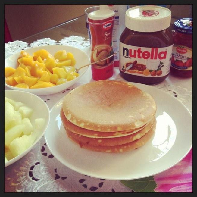 Trochę słodyczy na śniadanie :)   Przedstawiam prosty, szybki i sprawdzony przepis, który zawsze wychodzi.   Polskie Pancakes  Najlepiej smakują podawane ze świeżymi owocami, czekoladą, bitą śmietaną lub syropem klonowym   2 szklanki mąki 2 jajka 1 1/2 szklanki mleka 75 g rozpuszczonego masła 2-3 łyżeczki proszku do pieczenia 1/3 szklanki cukru pudru (czasem dodaje cukier waniliowy, wówczas zmniejszam ilość cukru pudru) szczypta soli  Mąkę przesiać przez sitko.   Jajka roztrzepać i wymieszać z mlekiem, proszkiem do pieczenia, cukrem pudrem i solą.  Masę dodać do mąki i dokładnie wymieszać żeby nie było grudek. Następnie dodać stopione masło. Wymieszać całość i odstawić na 15 minut.  Ciasto smażyć na małej patelni teflonowej bez dodatku tłuszczu, na średnim ogniu, tak aby ciasto miało szanse wyrosnąć i się nie przypaliło.  Delikatnie przewrócić na drugą stronę za pomocą szerokiej łopatki, gdy pancakes się zarumieni. Smażyć do momentu zarumienienia się drugiej strony.  Pyyycha :)
