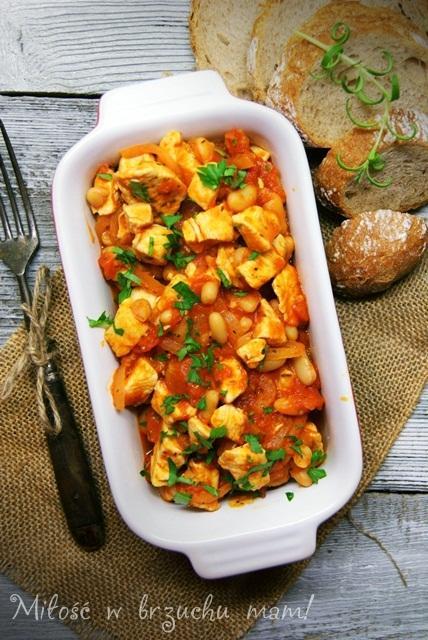 Kurczak z fasolką i pomidorami PRODUKTY: Podwójny filet z kurczaka 1 puszka białej fasolki 1 puszka krojonych pomidorów 1 cebula 2 ząbki czosnku 1,5 łyżeczki cukru Sól i pieprz 1 łyżeczka posiekanego rozmarynu 1 łyżeczka posiekanego tymianku Olej WYKONANIE: Kurczaka umyć, oczyścić i pokroić w kostkę. Na patelni rozgrzać olej. Usmażyć kurczaka oprószonego solą i pieprzem. Do mięsa dodać pokrojoną w piórka cebulę i drobno posiekany czosnek. Kiedy cebula się zeszkli dodajemy odsączoną fasolkę i pomidory. Danie dusimy pod przykryciem ok. 10 minut, pod koniec dodajemy cukier, sól, pieprz, rozmaryn i tymianek. Jeśli sos jest za gęsty podlewamy wszystko wodą. Podajemy z chrupiącym pieczywem.