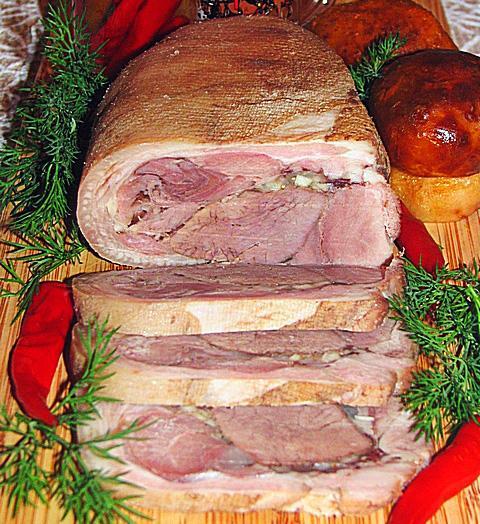 Noworoczna golonka na zimno – klik - zdjęcia Składniki :  • golonka - 1szt • mięso wołowe - 1 kg  • pieprz, liść laurowy  • sól  • Cebula – 1 • czosnek- 1 główka  UWAGA. Wraz z wołowiną lub zamiast niej można umieścić smażone grzyby.  Przygotowanie  Wymyć mięso, włożyc do zimnej wody/tyle by dobrze przykryła mięso/, doprowadzić do wrzenia, włożyć obraną cebulę, ziele angielskie, sól i gotować pod pokrywką na bardzo małym ogniu , przez co najmniej 4 godziny, a 5-6 godzin jest lepiej. Na 10 min przed końcem gotowania włożyć liść laurowy.  Po ugotowaniu wyjąć na talerz i zostawić do ostygnięcia. Rozciąć, wyciągnąć kość, przełożyć na zwiniętą na pół gazę. Posypać drobo pokrojonym czosnkiem, pieprzem, solą - jeśli to konieczne. W miejsce kości umieścić wołowinę. Przy pomocy gazy ciasno zrolować, włożyć do miski/garczka, położyć talerzyk i dobrze obciążyć. Odstawić do lodówki na noc. Kroić w plastry.