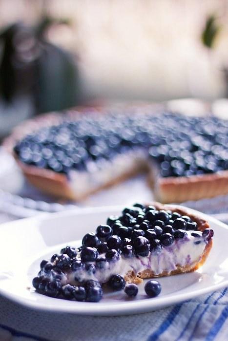 Kremowa tarta z jagodami Składniki: Ciasto kruche (tarta o średnicy 28 cm): • 220 g mąki • 1 jajko • 4 łyżki cukru pudru • łyżka ekstraktu z wanilii • 120 g masła Krem: • 250 g mascarpone • 200 ml śmietanki 30% • 1 łyżka ekstraktu z wanilii • 100 g białej czekolady • 2 łyżki cukru pudru Dekoracja: • jagody Wykonanie: Ciasto kruche:  Do garnka wkładamy cukier, masło i przesianą mąkę. Miksujemy aż zrobią się okruszki, dodajemy jajko i ekstrakt z wanilii i miksujemy raz jeszcze do połączenia się wszystkich składników. Lepimy z ciasta kulę, którą spłaszczamy, zwijamy w folię i wkładamy na pół godziny do lodówki. Następnie wyciągamy ciasto, rozwałkowujemy i przenosimy na formę o średnicy 28 cm. Dziurkujemy spód widelcem, wkładamy do lodówki na kolejne pół godziny, a w tym czasie nagrzewamy piekarnik do 180 stopni. Wyciągamy tartę z lodówki i przykrywamy folią aluminiową, obciążamy ryżem lub fasolą. Pieczemy 15 minut, zdejmujemy obciążenie. Zostawiamy tartę w piekarniku jeszcze na 13 minut. Wyciągamy i studzimy. Krem i dekoracja:  Czekoladę rozpuszczamy w misce nad parą wodną i odstawiamy do lekkiego przestudzenia. Śmietankę ubijamy. Pod sam koniec ubijania dodajemy cukier puder. Gdy śmietanka jest już ubita dodajemy w trzech częściach mascarpone i ekstrakt waniliowy i miksujemy na małych obrotach. Wlewamy czekoladę i mieszamy do połączenia się wszystkich składników. Wkładamy krem na pół godziny do lodówki, a po tym czasie wykładamy go na kruchy spód i dekorujemy jagodami.