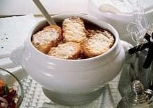 Zupa cebulowa zapiekana z serem Gruyere i grzankami Składniki: - 5 dużych cebul - 100 g masła - 2 łyżki tartego sera Gruyere - łyżka mąki - 4 ząbki czosnku - 2 litry esencjonaln...