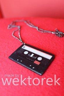 Wisiorek z kasetą magnetofonową.