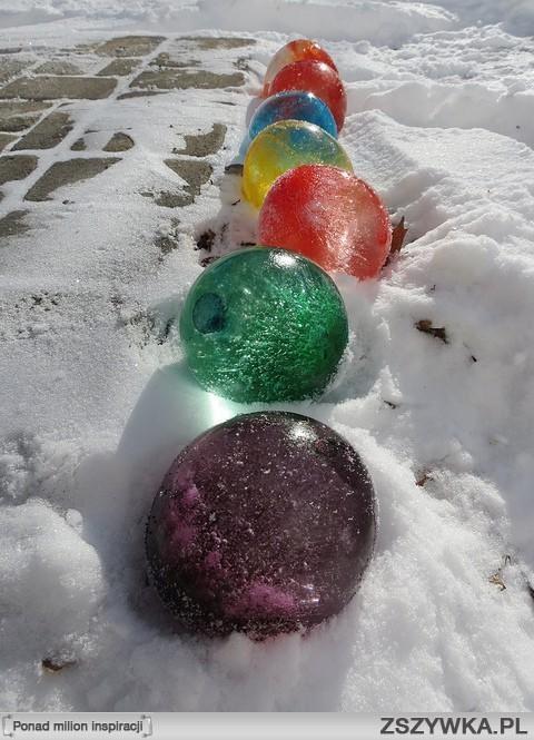 .Lodowe kule z balonów!.   Jest to niezwykła ozdoba każdego zimowego ogrodu :) Efekt niesamowity! Potrzebne nam będą kolorowe balony na wodę, woda i nożyczki (ew. karton, pudełko).   Wypełniamy nasze balony wodą, zawiązujemy, następnie umieszczamy w kartonie wyścielonym śniegiem, tak aby balony się nie przewracały. Zasypujemy balony śniegiem prawie całe i zostawiamy na noc na dworze (w ogrodzie/na balkonie). Na drugi dzień sprawdzamy czy są twarde-zamarzniete. Jeśli tak - za pomocą nożyczek ściągamy z nich plastik-powinien łatwo zejść, zostawiając kolor na naszych lodowych balonach:) super efekt z podświetleniem,np. wieczorem lub w pełnym słońcu. :)