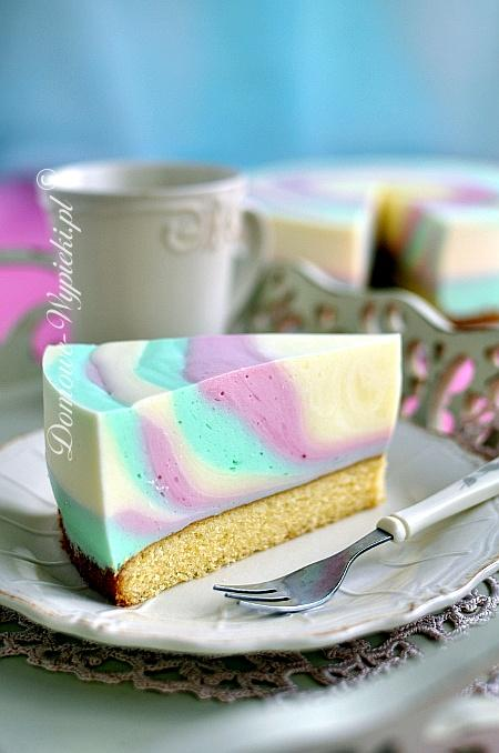 Zebra jogurtowa Składniki: Ciasto ucierane: 125g masła 100g cukru 2 łyżeczki cukru waniliowego 2 jajka 100g mąki pszennej 30g mąki lub skrobi ziemniaczanej 1,5 łyżeczki proszku do pieczenia 1 łyżka mleka Dodatkowo: 1 galaretka koloru czerwonego 1 galaretka koloru zielonego 1 galaretka koloru żółtego 500g jogurtu naturalnego 400g słodkiej śmietany 30- 36% Sposób przygotowania: Przygotować ciasto ucierane. Masło utrzeć z cukrem i cukrem waniliowym na puszystą masę. Dalej ubijając dodać po jednym jajku. Mąki wymieszać z proszkiem do pieczenia i razem z mlekiem dodać w dwóch/ trzech porcjach do ciasta. (Dodając mąki z mlekiem należy miksować krótko, tylko do połączenia się składników. Miksować na najniższych obrotach). Ciasto przełożyć do tortownicy (o średnicy 26cm) wyłożonej papierem do pieczenia. Piec w nagrzanym piekarniku ok. 20min. w temperaturze 180°C, do suchego patyczka. Ciasto pozostawić do całkowitego ostygnięcia. Każdą galaretkę rozpuścić osobno w 300ml wrzącej wody. Ostudzić. Jogurt podzielić na 3 części i każdą część dodać do ostudzonych galaretek. Dokładnie wymieszać trzepaczką. Gdy galaretki zaczną tężeć, ubić śmietanę na sztywno. Ubitą śmietanę podzielić na 3 części i wmieszać delikatnie do galaretek. Ciasto ułożyć na paterze. Założyć obręcz to tortu. Galaretki powinny mieć konsystencję delikatnie tężejącą. (Jeśli są płynne, poczekać chwilę).