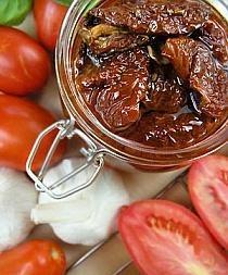 """Suszone pomidory na sposób domowy  -4 kg podłużnych, dojrzałych pomidorów """"San Marzano"""" -około 2 szklanki oleju słonecznikowego -8 ząbków czosnku -2 papryczki chilli -sól -kilka gałązek świeżego tymianku -kilka gałązek świeżej bazylii -kilka gałązek świeżego oregano   Pomidory myję, osuszam starannie, przekrawam na połówki. Usuwam nasionka.  Układam na blasze skórą do dołu, lekko solę i wstawiam do piekarnika z termoobiegiem (można je również przygotować w zwykłym piekarniku) nastawionym na 50 stopni. Suszę około 16 godzin (z przerwami kilkugodzinnymi - np. w nocy). Co jakiś czas sprawdzam stopień ususzenia. Pomidory powinny zmniejszyć znacznie swoją grubość, ale pozostać elastyczne, nie mogą wyschnąć """"na wiór"""".  Kiedy są gotowe, obieram czosnek i kroję na cienkie plasterki. Papryczki przekrawam wzdłuż i usuwam z nich nasionka.  Do słoików wkładam po kawałku papryczki, czosnek, następnie ususzone, jeszcze ciepłe pomidory. Pomiędzy kawałki pomidorów wkładam listki ziół. Pomidory nie powinny być zbyt ciasno upchane. Zalewam gorącym (ale nie wrzącym) olejem, słoikiem mocno potrząsam i stukam ostrożnie o blat stołu, by olej dostał się we wszystkie miejsca pomiędzy pomidorami. Zakręcam, stawiam do góry nogami na ściereczce i pozwalam spokojnie wystygnąć.  Można je przechowywać co najmniej kilka miesięcy w lodówce lub piwnicy."""