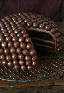 Tort czekoladowy 3 warstwowy przekładany kremem czekoladowym i ozdabiany orze...