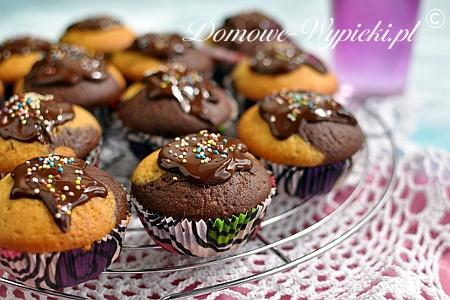 Muffinki marmurkowe Proste i szybkie dwukolorowe muffinki waniliowo- kakaowe. Składniki: 250g mąki pszennej 80g cukru 4 łyżeczki cukru waniliowego 2 łyżeczki proszku do pieczenia 200ml mleka 80ml oleju 2 jajka Dodatkowo: 2 łyżki mleka 1 łyżka kakao Sposób przygotowania: W jednej misce wymieszać mąkę, cukier, cukier waniliowy i proszek do pieczenia. W drugiej misce wymieszać mleko, olej i jajka. Kolejno wymieszać trzepaczką składniki z obu misek. (Nie mieszać długo, tylko do połączenia składników). Ciasto podzielić na pół. Do jednej części wmieszać kakao i mleko. Formę na muffinki wyłożyć papilotkami. Ciasto nakładać po łyżeczce na przemian jasne z ciemnym. Muffinki piec w nagrzanym piekarniku około 25 min. w temperaturze 180°C.