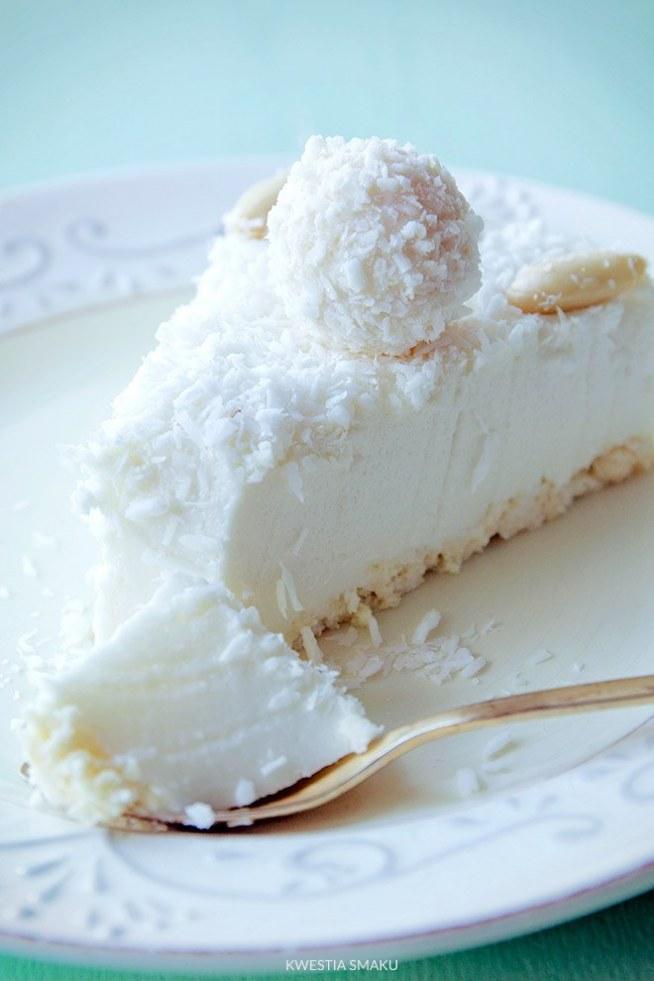 Sernik Raffaello na zimno :)  Składniki:  Spód: • 100 g wafelków kokosowych w białej czekoladzie typu princessa  Masa kokosowa: • 250 g serka mascarpone • 1 i 1/2 szklanki (225 g) cukru pudru • 2 puszki mleka kokosowego (2 x 400 ml) • 250 g twarogu sernikowego lub jogurtu greckiego • 200 g białej czekolady • 4 łyżki likieru amaretto • 6 łyżek likieru kokosowego (np. domowego) • 2 i 1/2 łyżki żelatyny + 3 łyżki wody     Dekoracja: • około 50 g wiórków kokosowych • opcjonalnie: gotowe pralinki kokosowe, obrane migdały   Przygotowanie:  Wafelki pokruszyć i wyłożyć równą warstwą na spód tortownicy o średnicy 24-25 cm, nie trzeba uklepywać. Serek mascarpone ubić z cukrem pudrem (około 1-2 minuty, do podwojenia objętości), jeśli nie mamy miksera możemy użyć trzepaczki lub rózgi. Teraz kolejno będziemy dodawać resztę składników za każdym razem mieszając trzepaczką. Dodać twaróg i używając trzepaczki energicznie mieszać aż masa będzie jednolita, dodać mleko kokosowe i powtórzyć połączenie składników za pomocą trzepaczki. Czekoladę roztopić i stopniowo, po łyżce, dodawać do niej masę kokosową (w ten sposób dodać około 6-7 łyżek masy kokosowej), wraz z każdą dodaną łyżką mieszać czekoladę trzepaczką. Dopiero taką zahartowaną czekoladę dodać do reszty masy i wymieszać trzepaczką. Dodać likiery a następnie żelatynę: najpierw namoczyć żelatynę w zimnej wodzie (10 minut), najlepiej w metalowym garnuszku, później na małym ogniu podgrzewać mieszając aż żelatyna całkowicie się rozpuści, nie zagotowywać. Dodawać do niej po łyżce masę kokosową (w sumie około 6-7 łyżek) za każdym razem mieszając, postępujemy tak samo jak w przypadku dodawania białej czekolady. Po dodaniu likieru i żelatyny masę wymieszać i łyżką wyłożyć na wafelki (nie wylewać na raz całej masy bo wafelki się przemieszają). Wstawić do lodówki na kilka godzin. Gdy deser będzie całkowicie zastygnięty, obkroić nożem i zdjąć obręcz. Wierzch posypać wiórkami kokosowymi i udekorować migdałami lub pralinkami.  Smacznego :)