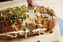 Chleb nacinamy w kratkę, nie kroimy do końca, żeby bochenek pozostał w jednym kawałku. Pomiędzy nacięcia wkładamy pokrojony żółty ser, ilość zależy od upodobań, całość polewamy ...