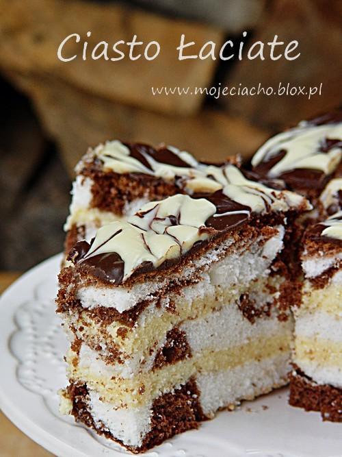 """Ciasto łaciate   Składniki na ciasto jasne:      6 białek     200 g cukru     50 g mąki pszennej     150 g mąki ziemniaczanej     1 łyżka octu     1/2 łyżeczki proszku do pieczenia  Białka ubijamy na sztywną pianę, dodajemy stopniowo cukier- ubijamy na sztywną bezę. Następnie dodajemy stopniowo pozostałe składniki i lekko, ale dokładnie mieszamy.   Składniki na ciasto ciemne:      6 jaj     3/4 szklanki cukru     1 szklanka mąki pszennej     2 łyżki kakao     1 łyżeczka proszku do pieczenia  Białka ubijamy na sztywno, pod koniec dodajemy cukier i miksujemy na bezę. Następnie dodajemy żółtka i mieszamy. Na koniec dodajemy mąkę pszenną, przesianą z kakao i proszkiem do pieczenia, delikatnie, ale dokładnie mieszamy.   Składniki na masę z sera gotowanego:      1 kg sera białego (zmielonego)     1 szklanka cukru (ew. do smaku dodać więcej)     6 żółtek     3 łyżeczki czubate mąki ziemniaczanej (dałam 3 łyżki)     cukier waniliowy     1/2 szklanki mleka     200 g masła lub margaryny  Ser, masło, cukier, żółtka (ja żółtka dodaję na końcu, zmiksowane z mąką i mlekiem) wkładamy do dużego garnka, podgrzewać, aż wszystkie składniki się rozpuszczą. ?Mąkę rozpuszczamy w mleku i wlewamy do gotującej się masy serowej, gotować kilka minut całość, aż masa zgęstnieje.   Ponadto do dekoracji:      czekolada deserowa     3/4 czekolady mlecznej     mleko do roztapiania czekolady (wlewałam po ok. 30 ml, lub dolewałam na wyczucie)     biała czekolada  Rozpuściłam obie ciemne czekolady (deserową i mleczną) w kąpieli wodnej, wylałam na ciasto, już lekko odparowaną. Osobno rozpuściłam białą, nakładałam ją ,,kępkami """" po cieście i mieszałam z ciemna za pomocom wykałaczki, robić wzory.   Wykonanie:  Ciasto piekłam w blaszce o wymiarach 24 x 35 cm, wyłożone papierem do pieczenia. Najpierw wykładamy ciasto ciemne po łyżce, obok białe i tak na przemian. Następnie na ciasto białe kładziemy łyżkę ciemnego, a na ciemne białe. Wierzch lekko wyrównujemy łyżką i pieczemy w piekarniku ok. 45 minut (u mn"""