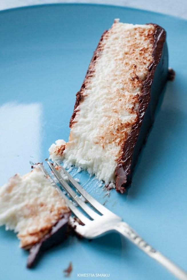 """Sernik Bounty na zimno z wiórkami kokosowymi i czekoladą  Deser można zrobić na spodzie z ciasteczek np. kruchych z kawałkami czekolady. Zamiast twarogu można użyć serka mascarpone, wówczas pomijamy w przepisie masło (sernik będzie bardziej kremowy i mniej """"kwaskowaty"""").     Składniki:  • 400 ml mleka kokosowego • 200 g wiórków kokosowych • 100 g masła • 150 g cukru pudru • 30 g cukru wanilinowego • 3 łyżki likieru kokosowego (opcjonalnie) • 2 łyżki żelatyny • 500 g zmielonego twarogu sernikowego lub serka mascarpone   Spód i polewa czekoladowa: 150 g czekolady mlecznej 3 łyżki oleju roślinnego    Przygotowanie: Do rondelka wlać mleko kokosowe z puszki i podgrzać. Gdy zacznie się gotować dodać wiórki kokosowe, wymieszać, zmniejszyć ogień i potrzymać wszystko na minimalnym ogniu pod przykryciem przez około 5-10 minut. Sprawdzić czy wiórki nie przywierają do dna, w razie potrzeby zamieszać. Odstawić z ognia, dodać masło i mieszać aż się rozpuści, następnie dodać cukier puder, cukier wanilinowy, likier kokosowy i wymieszać. Zostawić pod przykryciem na czas przygotowania reszty składników. Żelatynę wsypać do metalowego kubeczka, wlać 3 łyżki wody i zostawić do namoczenia na około 10 minut. Następnie dodać jeszcze 3 łyżki wody i mieszając rozpuścić wszystko na malutkim ogniu uważając aby nie zagotować żelatyny. Do masy kokosowej dodać ser i wymieszać. Żelatynę dodać do masy kokosowej, ale nie bezpośrednio, najlepiej dodawać najpierw po łyżce masę kokosową do żelatyny za każdym razem mieszając do połączenia się składników, później przełożyć do reszty masy kokosowej i dokładnie wymieszać. 50 g czekolady roztopić z 1 łyżką oleju i rozsmarować na spodzie tortownicy o średnicy około 23 cm wyłożonej papierem do pieczenia. Od razu wyłożyć łyżką masę kokosową, delikatnie wyrównać powierzchnię i wstawić do lodówki do stężenia (minimum 3 godziny). Gdy masa już stężeje, obkroić sernik nożem, zdjąć obręcz i polać resztą roztopionej czekolady z resztą oleju, rozprowadzić polewę po po"""