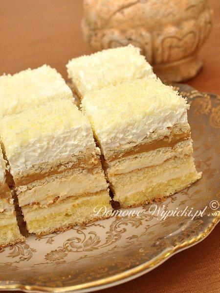 Ciasto balowe  Ciasto jest delikatne i lekkie, proste w przygotowaniu. Jest bogate w różnego rodzaju warstwy: biszkopt, masa budyniowa, herbatniki, masa krówkowa, krakersy, bita śmietana. Jest słodkie, sycące, pyszne, choć kaloryczne. Ciasto należy przygotować, co najmniej dzień wcześniej, aby herbatniki i krakersy zmiękły. Wtedy ciasto będzie rozpływać się dosłownie w ustach. Polecam.  Składniki: Biszkopt: •4 jaja •½ szklanki mąki pszennej •½ szklanki mąki ziemniaczanej •¾ szklanki cukru •1 łyżeczka proszku do pieczenia  Masa budyniowa: •4 żółtka •¾ szklanki cukru •2 łyżeczki cukru waniliowego •2 szklanki mleka •2 kopiate łyżki mąki ziemniaczanej •250g masła  Poncz: •ok. 1 ½ szklanki soku pomarańczowego  Dodatkowo: •1 puszka masy krówkowej (500g) lub puszka słodkiego mleka skondensowanego •ok. 140g herbatników (20sztuk) •niecałe 100g krakersów (20 sztuk) •400- 500ml słodkiej śmietany 30- 36% •2 opakowania śmietan-fix •ok. 50- 100g dowolnej czekolady (u mnie biała)  Sposób przygotowania: 1.Jeśli mamy puszkę słodkiego mleka skondensowanego, należy gotować ją w garnku z wodą na małym ogniu przez 3 godz. (Puszka musi być cała pokryta wodą). 2.Przygotować biszkopt. Oddzielić żółtka od białek. Białka ubić na sztywną pianę. Dalej ubijając dodać stopniowo cukier. Na końcu dodać po jednym żółtku. W miseczce wymieszać obie mąki z proszkiem do pieczenia. Przesiać do masy jajecznej i delikatnie wymieszać. Formę prostokątną o wymiarach około 35x24cm wysmarować masłem lub margaryną i posypać bułką tartą. Gotowe ciasto przełożyć do formy i piec w nagrzanym piekarniku 20- 25min w temperaturze 200°C. Biszkopt po upieczeniu ostudzić i przeciąć na pół tak, aby powstały dwa blaty. 3.Przygotować masę budyniową. 1 ½ szklanki mleka i cukier zagotować. Pozostałe mleko wymieszać dokładnie z żółtkami, cukrem waniliowym i mąką ziemniaczaną. Dodać do gotującego się mleka, szybko mieszając, aby nie powstały grudki. Chwilkę gotować (około 1 min), aż budyń zgęstnieje. Pozostawić do ostygnięcia. 