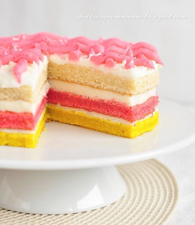 Ciasto anielskie:   Składniki na ciasto:      250g masła w temperaturze pokojowej     1 ¼ szklanki drobnego cukru     4 jajka (osobno białka  i żółtka)     1 ½ szklanki mąki pszennej     1 łyżeczka proszku do pieczenia     3-4 łyżki mleka     1 łyżeczka ekstraktu wanilii     barwnik żółty i czerwony   Krem:      2 szklanki cukru pudru     ½ kostki masła (125g)     ziarenka z pół laski wanilii   Cukier puder, masło i ziarenka wanilii ucieramy mikserem na gładki krem  Polewa:      2 szklanki cukru pudru     3 łyżki masła     1-3 łyżki gorącej wody     dodatkowo barwnik czerwony   Cukier puder, masło oraz gorącą wodę miksujemy na gładką masę, do mniejszej miseczki odkładamy 2-3  łyżki polewy, dodajemy barwnik czerwony ale tylko tyle aby uzyskać kolor różowy, przekładamy do rękawa cukierniczego.  Wykonanie ciasta:      masło i cukier ucieramy  na jasną kremową masę, dodajemy po kolei żółtka nie przerywając miksowania,     następnie stopniowo do masy dodajemy mąkę wymieszaną z proszkiem do pieczenia, mleko i ekstrakt wanilii     w drugim naczyniu ubijamy białka ze szczyptą soli  na sztywną pianę, dodajemy do ciasta, całość delikatnie mieszamy     ciasto dzielimy na trzy równie części do jednej dodajemy żółty barwnik, do drugiej czerwony( tylko tyle aby uzyskać różowy kolor) , trzecią części pozostawiamy w naturalnym kolorze     tortownicę (20cm, ja użyłam większą dlatego ciasto jest niższe) wykładamy papierem do pieczenia i po kolei pieczemy blaty ciasta każdy około 25-35 w temperaturze 180ºC, gotowe studzimy na kratce     na paterze układamy najpierw żółty blat,  na którym rozsmarowujemy część kremu, przykrywamy różowym blatem smarujemy pozostałą częścią kremu, nakładamy ostatni blat który smarujemy polewą , a wierzch dekorujemy dowolny wzorem różową polewą i gotowe.