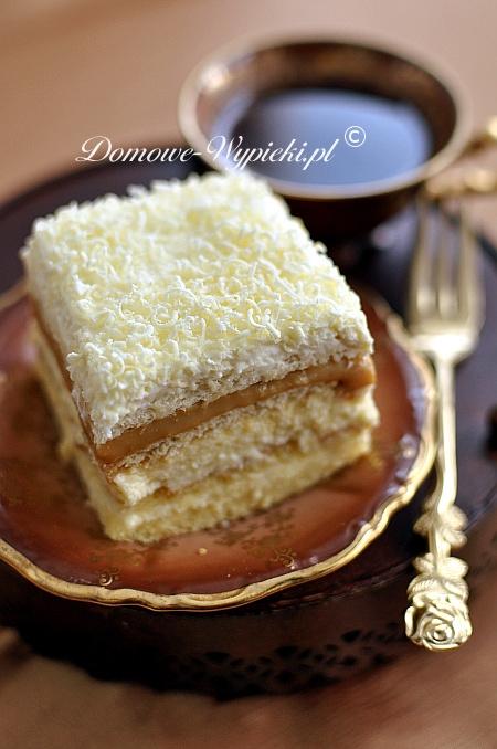 Biszkopt: 4 jaja ½ szklanki mąki pszennej ½ szklanki mąki ziemniaczanej ¾ szklanki cukru 1 łyżeczka proszku do pieczenia Masa budyniowa: 4 żółtka ¾ szklanki cukru 2 łyżeczki cukru waniliowego 2 szklanki mleka 2 kopiate łyżki mąki ziemniaczanej 250g masła Poncz: ok. 1 ½ szklanki soku pomarańczowego Dodatkowo: 1 puszka masy krówkowej (500g) lub puszka słodkiego mleka skondensowanego ok. 140g herbatników (20sztuk) niecałe 100g krakersów (20 sztuk) 400- 500ml słodkiej śmietany 30- 36% 2 opakowania śmietan-fix ok. 50- 100g dowolnej czekolady (u mnie biała) Sposób przygotowania: Jeśli mamy puszkę słodkiego mleka skondensowanego, należy gotować ją w garnku z wodą na małym ogniu przez 3 godz. (Puszka musi być cała pokryta wodą). Przygotować biszkopt. Oddzielić żółtka od białek. Białka ubić na sztywną pianę. Następnie dodać stopniowo cukier. Dalej miskując, dodać po kolei po jednym żółtku. W miseczce wymieszać obie mąki z proszkiem do pieczenia. Przesiać do masy jajecznej i delikatnie wymieszać. Formę prostokątną o wymiarach około 35x 24cm wysmarować masłem lub margaryną i posypać bułką tartą (lub dno formy wyłożyć papierem do pieczenia). Gotowe ciasto przełożyć do formy i piec w nagrzanym piekarniku ok. 20- 25min. w temperaturze 200°C. Biszkopt po upieczeniu ostudzić i przeciąć na pół tak, aby powstały dwa blaty. Przygotować masę budyniową. 1 ½ szklanki mleka i cukier zagotować. Pozostałe mleko wymieszać dokładnie z żółtkami, cukrem waniliowym i mąką ziemniaczaną. Dodać do gotującego się mleka, szybko mieszając, aby nie powstały grudki. Chwilkę gotować (około 1 min), aż budyń zgęstnieje. Pozostawić do ostygnięcia. Miękkie masło utrzeć mikserem na puszystą masę. Dalej miksując dodawać stopniowo zimny budyń. Jeden blat biszkoptu włożyć do formy i nasączyć połową ponczu. Nałożyć niegrubą warstwę masy budyniowej. Przykryć drugim blatem biszkoptu i go nasączyć. Nałożyć resztę masy. Na masę wyłożyć herbatniki. Na herbatnikach rozsmarować masę krówkową, na masie ułożyć krakersy, n