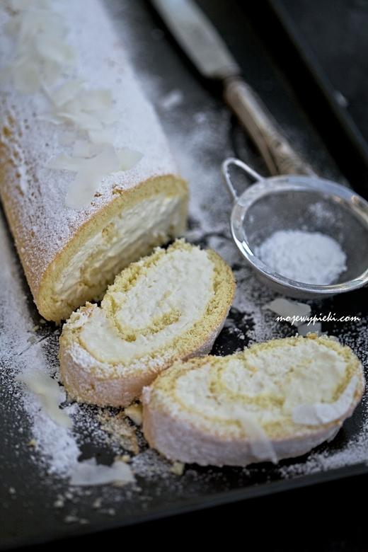 BISZKOPTOWA ROLADA KOKOSOWA  Składniki na biszkopt:  3 duże jajka 50 g drobnego cukru do wypieków 40 g mąki pszennej 40 g skrobi (mąki) ziemniaczanej pół łyżeczki proszku do pieczenia szczypta soli Wszystkie składniki powinny być w temperaturze pokojowej.  Białka oddzielić od żółtek. Białka ubić na sztywną pianę ze szczyptą soli. Dodawać stopniowo cukier, dalej ubijając. Dodawać po jednym żółtku, i dalej ubijać.  Mąki przesiać z proszkiem. Dodać do ubitej masy i delikatnie wymieszać szpatułką, by piana nie 'siadła'.  Blachę prostokątną o niewysokich brzegach (o wymiarach 43 x 28 cm) wyłożyć papierem do pieczenia. Na papier wyłożyć masę, wyrównać.  Przygotować lniany ręczniczek kuchennym, oprószyć drobnym cukrem.   Blaszkę z ciastem włożyć do piekarnika rozgrzanego do 170ºC i piec przez około 12 minut. Wyjąć z piekarnika, odwrócić do góry dnem, ciasto przełożyć na lniany ręczniczek kuchenny, usunąć papier do pieczenia. Następnie roladę zwinąć wzdłuż dłuższego boku (razem z ręcznikiem), odstawić do ostudzenia.   Krem kokosowy:  500 g serka mascarpone 250 ml śmietanki kokosowej 22%* 3/4 szklanki wiórków kokosowych 1 łyżka likieru Malibu 3 łyżki cukru pudru Dodatkowo:  płatki kokosowe, do posypania  cukier puder, do oprószenia Wszystkie składniki powinny być schłodzone.  Wszystkie składniki na krem kokosowy umieścić w misie miksera i zmiksować, pod sam koniec miksowania dodając wiórki kokosowe. Nie miksować zbyt długo, tylko do połączenia się składników.  *Zamiast śmietanki kokosowej można wykorzystać mleko kokosowe: schłodzone mleko ostrożnie wyjąć z lodówki, odwrócić puszkę dnem do góry, otworzyć, wodę kokosową przelać do osobnego naczynia (nie będzie nam potrzebna w przepisie). Z puszki wyjąć pozostałą gestą śmietankę kokosową, wykorzystać ją w przepisie.   Wykonanie:  Wystudzoną roladę odwinąć, usunąć ręcznik. Na biszkopt wyłożyć krem. Zwinać w taki sam sposób, jak była zwinięta rolada wraz z ręczniczkiem, czyli wzdłuż dłuższego boku. Schłodzić w lodówce przez minim