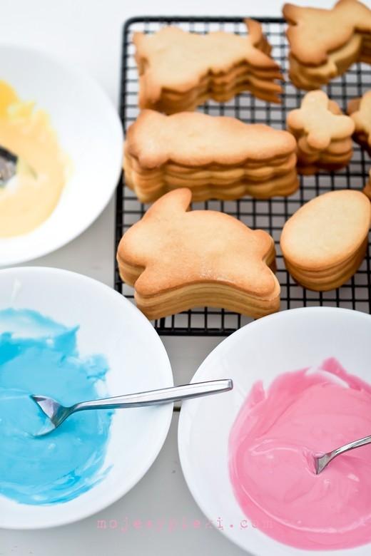 LUKIER KRÓLEWSKI (ROYAL ICING) Składniki na lukier królewski: 90 g białka 445 g cukru pudru 5 - 7 kropli soku z cytryny (może być w butelce) lub 4 - 5 kropli białego octu winnego Białka oddzielić od żółtek z jednodniowym wyprzedzeniem. Przelać je do czystego, suchego naczynia, przykryć folią spożywczą i pozostawić w lodówce na całą noc. Dzięki temu białko się wzmocni. Przed samym ubijaniem przecedzić białko przez drobne sitko, np. od herbaty. W misie miksera umieścić wszystkie składniki na lukier. Ucierać przez 10 - 20 minut na najniższych obrotach miksera przy użyciu końcówki mieszającej w kształcie litery 'K'. Nie wolno ubijać zbyt szybko - spowoduje to napowietrzenie cukru i utworzą się pęcherzyki powietrza, które powodują pękanie lukru. W gotowym lukrze nie powinno być najmniejszych grudek. Gotowy lukier nie spływa ze szpatułki, ale delikatnie się na niej zagina. Jest to podstawowy przepis do lukrowania dużych, płaskich powierzchni na ciasteczkach, dobrze się rozprowadza. Z papieru do pieczenia zrobić tutkę, odciąć końcówkę, wypełnić lukrem królewskim i dekorować ciasteczka. Ja do dekoracji używam jednorazowych rękawów cukierniczych i tylek. Uwaga: do wyciskania kształtów, kwiatków, postaci, szczegółów - na każde 175 g gotowego powyższego lukru należy dodać 1 łyżkę przesianego cukru pudru i wymieszać (nie ubijać). Wtedy lukier jest bardziej gęsty. W każdym przypadku, jeśli uważacie, że lukier jest zbyt rzadki - należy dodać więcej cukru pudru, jeśli zbyt gęsty - więcej białka. Korzystałam z przepisu na najlepsze waniliowe kruche ciasteczka do wycinania. Niektóre z ciasteczek, oprócz lukru zostały przykryte warstwą drobnego cukru do wypieków, dla dodania dodatkowej tekstury.
