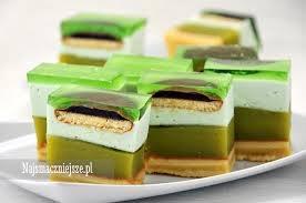 A to cudo będę piekła ja  Ciasto Shrek  Zielone, delikatne ciasto biszkoptowe z zieloną masą budyniową, zieloną galaretką, lekko zielonkawą pianką i delicjami. Ciasto jest zielone tak, jak zielony jest ogr Shrek. Stąd też jego nazwa ;). Ciasto jest bardzo podobne do ciasta Kubuś. Składniki: Biszkopt: 3 jajka 60g mąki pszennej 60g mąki ziemniaczanej 100g cukru ½ łyżeczki proszku do pieczenia 1 łyżka wody Masa budyniowa: 900ml zielonego soku (Kubuś, Pysio) 3 budynie waniliowe bez cukru 2 łyżki cukru 200g masła Pianka: 1 galaretka zielona (np. agrestowa) 500ml słodkiej śmietany 30- 36% 2 łyżki cukru pudru Dodatkowo: ok. 300g delicji 1 galaretka zielona (np. agrestowa) Sposób przygotowania: Przygotować biszkopt. Oddzielić żółtka od białek. Białka ubić na sztywną pianę. Dalej ubijając dodać stopniowo cukier. Na końcu dodać po jednym żółtku. W miseczce wymieszać obie mąki z proszkiem do pieczenia. Przesiać do masy jajecznej i delikatnie wymieszać. Dodać wodę. Formę prostokątną o wymiarach około 35x24cm wysmarować margaryną i posypać mąką lub bułką tartą. Gotowe ciasto przełożyć do formy i piec w nagrzanym piekarniku ok. 20min w temperaturze 180°C. Pozostawić do ostygnięcia. Przygotować masę budyniową. Większą część soku zagotować z cukrem. Pozostały sok wymieszać dokładnie z budyniami (proszkiem). Dodać do gotującego się soku, szybko mieszając, aby nie powstały grudki. Chwilkę gotować (około 1 min), aż budyń zgęstnieje. Pozostawić do ostygnięcia. Miękkie masło utrzeć mikserem na puszystą masę. Dalej miksując dodawać stopniowo zimny budyń. Na ostudzony biszkopt wyłożyć masę budyniową. Na masie poukładać delicje. Ciasto wstawić do lodówki. Przygotować piankę. Galaretkę rozpuścić w szklance gorącej wody. Pozostawić do ostygnięcia. Śmietanę ubić na sztywno. Pod koniec ubijania dodać cukier puder. Kolejno, dalej miksując, dodać stopniowo tężejącą galaretkę. Wyłożyć na delicje. Wstawić do lodówki. Gdy pianka stężeje, przygotować galaretkę według przepisu na opakowaniu. Zimną ga
