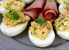 6 jajek ugotowanych na twardo 4 plasty szynki wieprzowej 2 łyżki majonezu lub kremowego serka twarogowego sól, pieprz świeży koperek Obrane jajka kroimy na połówki, wyjmujemy żó...