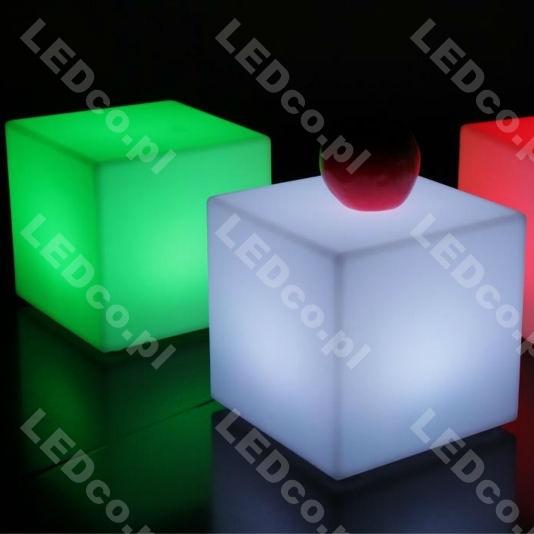 Świecące meble kostki LED QUADRUM XL są idealnym wyposażeniem każdego nowoczesnego ogrodu, balkonu, holu czy korytarza. Mogą być ustawione zarówno w pokoju dla dziecka jak również w klubie czy hotelu. Pełnią one role siedzeń ale można je wykorzystać również jako element dekoracji, wystroju lub lamp oświetlających  np. drogę do pensjonatu. Kostki LED dają szczególny i niepowtarzalny efekt.  Kostka QUADRUM XL może być zasilana na dwa sposoby: 1. Za pomocą kabla podłączanego bezpośrednio do sieci. Kabel ma długość 2,9m, zakończony jest wtyczką do gniazdka. Zaletą tego rozwiązania jest stałe podłączenie do sieci co sprawia ze nie trzeba się martwić o rozładowanie kostki. W tej wersji zasilania możemy wybrać następujące barwy podświetlenia:      biała ciepła     biała zimna     RGB kolory zmieniane za pomocą pilota lub różnych trybów  2. Za pomocą bezprzewodowego modułu z wbudowanymi akumulatorkami. W pełni naładowany akumulator pozwala na pracę 7-8 godzin (w zależności od trybu i jasności świecenia). Ładowanie akumulatora trwa do kilku godzin, Quadrum może jednak pracować w trakcie ładowania. W zestawie znajduje się pilot z baterią oraz ładowarka. Kostki LED zbudowane są ze specjalnego utwardzonego tworzywa przez co są wytrzymałe. Kostkę LED ustawić można aby świeciła jednolitym kolorem lub zmieniała kolory z różną częstotliwością przechodząc z jednego w inny. Do wyboru jest 16 kolorów świecenia np.: czerwony, niebieski, zielony, biały, fioletowy, turkusowy, żółty, biały itd. Kolory można również pojaśniać lub pociemniać. Funkcje i kolory zmieniać można za pomocą bezprzewodowego pilota lub przyciskami na spodzie kostki. Mając wiele kostek można zmieniać ich kolory i tryby świecenia jednym pilotem.