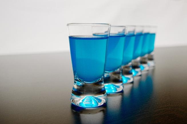 KAMIKADZE   Składniki: 80 ml wódki czystej 40 ml blue curacao lub Bols Blue 40 ml soku z cytryny (świeżo wyciskanego) lód  Przygotowanie:  Wlej wszystkie składniki do shakera wypełnionego lodem. Kilka razy mocno wstrząśnij. Przelej przecedzoną zawartość do kieliszków (podane tu proporcje wystarczą na cztery kieliszki po 40 ml).