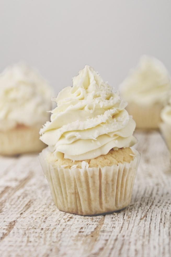 babeczki kokosowe ciasto (ok. 8 sztuk): 200 g mąki pszennej 30 ml kwaśnej śmietany 4 łyżeczki mleka kokosowego 1 łyżeczka proszku do pieczenia 90 g masła (w temp. pokojowej) 60 ml kremówki 36% 30 ml mleka 125 g cukru 1 białko  Mąkę przesiać z proszkiem do pieczenia do misy miksera, dodać posiekane masło. kwaśną śmietanę, kremówkę, białko, mleko, mleko kokosowe, cukier i wyrabiać mikserem na najniższych obrotach, tylko do połączenia składników. W formie do babeczek umieścić papilotki. Ciasto wykładać do 2/3 wysokości papilotek. Piec w 180C przez 25-30 minut. Wyjąć i odstawić do całkowitego wystudzenia.   krem: 200 g mascarpone  200 g kremówki 36% 4 łyżki cukru pudru 3 łyżeczki mleka kokosowego wiórki kokosowe (do dekoracji)  Kremówkę ubić na sztywno, dodać mascarpone, cukier, mleko kokosowe i dokładnie wymieszać. Gotowy krem przełożyć do rękawa cukierniczego z dowolną końcówką i wyciskać na wystudzone babeczki. Całość posypać wiórkami kokosowymi. Podawać.
