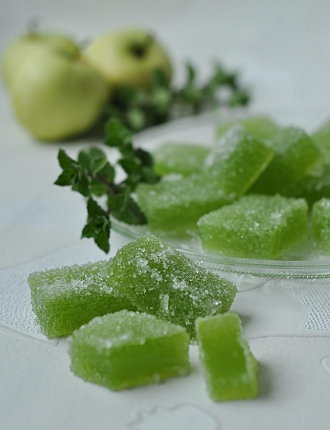 Jabłkowe galaretki w cukrze  Składniki: 500 ml soku jabłkowego z papierówek ½  szklanki cukru 1 opakowanie galaretki jabłkowo-miętowej 1,5 łyżeczki żelatyny  Cukier do obtaczania, najlepiej kryształ  Przygotowanie: W rondelku mieszamy cukier z sokiem jabłkowym, podgrzewamy na małym ogniu ciągle mieszając, gotujemy chwilkę aż sok zgęstnieje, wyłączamy. Dodajemy do soku galaretkę i żelatynę wcześniej namoczoną w 2 łyżkach wody, dokładnie mieszamy wszystko, aż rozpuszczą się wszystkie składniki. Kwadratową foremkę (25 x 25) wykładamy folią aluminiową, wlewamy masę , studzimy i wstawiamy na noc do lodówki do stężenia.  Rano przekładamy z foremki galaretkę na deseczkę i kroimy ją ostrym nożem w kwadraty.  Każdą galaretkę obtaczamy dokładnie w cukrze i zostawiamy w temperaturze pokojowej , aż cukier przyschnie, a galaretki będą sprężyste i nie będą się kleić.  Galaretki są świetnym słodkim dodatkiem do kawy.  Dzieciom też będą smakować