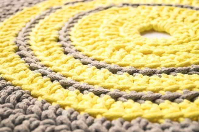 Ręcznie robiony dywan w kolorze żółtym i szarym.