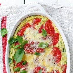 """ZAPIEKANY OMLET Z CUKINIĄ, POMIDORAMI I SEREM SKŁADNIKI 1-2 PORCJE 4 jajka 1 łyżka posiekanej bazylii 130 g cukinii 60 g miękkiego sera (np. gruyere, cheddar, innego """"żółtego"""") 1 średniej wielkości pomidor sól 1/2 łyżki masła DO PODANIA: świeżo mielony pieprz listki bazylii opcjonalnie: oliwa extra vergine PRZYGOTOWANIE Piekarnik nagrzać do 180 stopni C. Nieduże i niewysokie naczynie żaroodporne posmarować masłem. Jajka wbić do miski, doprawić solą, dodać bazylię i roztrzepać rózgą lub widelcem. Zetrzeć na drobnej tarce cukinię oraz 2/3 ilości sera, wymieszać z masą jajeczną. Małe naczynie do zapiekania posmarować masłem. Wylać masę jajeczną, na wierzchu ułożyć plasterki pomidora, doprawić je solą. Zapiekankę posypać resztą tartego sera. Wstawić do piekarnika i piec przez około 20 minut lub do ścięcia się masy. Podawać ze świeżo mielonym pieprzem, świeżą bazylią i - opcjonalnie - skropione oliwą extra vergine."""
