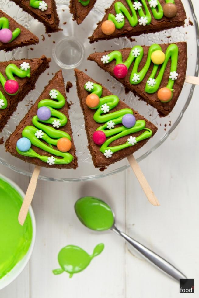 SKŁADNIKI  na 8 choinek  Ciasto: 100 g masła w temperaturze pokojowej 100 g cukru 100 g gorzkiej czekolady (min. 70% kakao) 2 jajka 100 g mąki pszennej 1 łyżeczka proszku do pieczenia 2 łyżki mleka Dodatkowo: 300 g cukru pudru zielony barwnik spożywczy kilka kropli soku z cytryny kolorowe czekoladowe cukierki, np. Smarties cukrowe gwiazdki 8 drewnianych patyczków   * PRZYGOTOWANIE  Ciasto  Masło utrzyj z cukrem na białą masę za pomocą miksera. Wbij pierwsze jajko i zmiksuj z masą, następnie wbij drugie i znowu zmiksuj. Czekoladę rozpuść w kąpieli wodnej i odstaw do wystudzenia. Dodaj następnie do maślanej masy i wymieszaj za pomocą miksera. Wsyp mąkę wymieszaną uprzednio z proszkiem do pieczenia, wlej mąkę i wymieszaj szpatułką. Ciasto wlej do okrągłej formy o średnicy 20 cm, pokrytej uprzednio papierem do pieczenia. Piecz ok. 30 minut w 180ºC do suchego patyczka. Wyjmij i odstaw do wystudzenia.   Dekoracja  Ciasto oddziel od papieru i podziel na 8 równych trójkątnych części. W każdy kawałek wbij drewniany patyczek. Przygotuj lukier, dolewając do cukru pudru odrobinę wrzątku, kilka kropli soku z cytryny i energicznie mieszając. Dodaj odpowiednią ilość zielonego barwnika, aż uzyskasz żądany kolor. Lukier przelej do małego woreczka foliowego. Natnij jego rożek i udekoruj wierzch ciasta, formując szlaczek jak na zdjęciach. Ciasto ozdób cukierkami i cukrowymi gwiazdkami. Odstaw do zastygnięcia lukru.