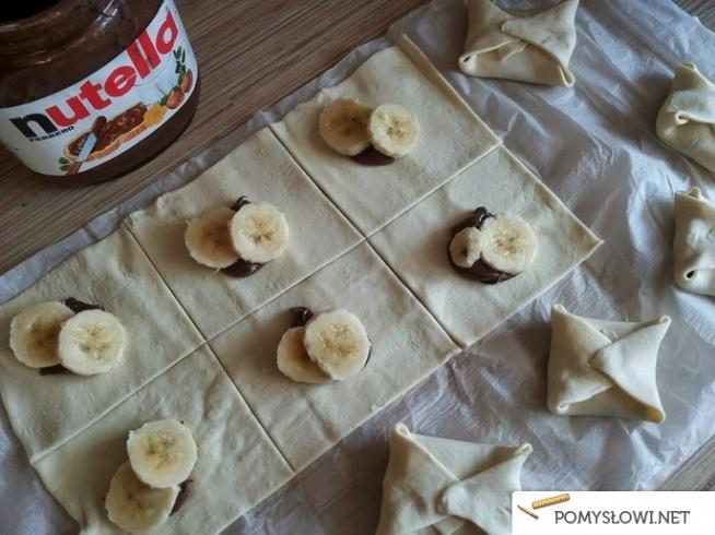 koperty z nutellą i bananem SKŁADNIKI: - 1 opakowanie ciasta francuskiego - 12 łyżeczek nutelli - banan (pokrojony na 24 części)  SPOSÓB PRZYGOTOWANIA: 1. Ciasto francuskie pokroić na 12 równych kwadracików. 2. Na każdy kawałek położyć po łyżeczce nutelli i dwa plasterki banana. 3. Zawinąć rogi ciasta, tak aby powstały koperty. 4. Piec w piekarniku nagrzanym do 180 stopni przez 25 min., do momentu, aż się zarumienią. 5. Wystudzić i obsypać cukrem pudrem.
