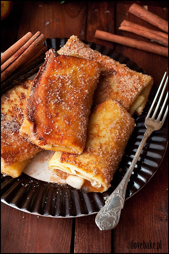 NALEŚNIKI Z JABŁKAMI W POSYPCE CUKROWEJ Z CYNAMONEM  SKŁADNIKI NA CIASTO NALEŚNIKOWE: 1 szklanka mąki tortowej 2 jajka 1/2 szklanki mleka 1/2 szklanki wody (może być gazowana) 1 łyżka masła, roztopionego szczypta soli  SKŁADNIKI NA NADZIENIE JABŁKOWE:  4 jabłka, najlepiej lekko kwaśne 1/2 szklanki wody 1/4 szklanki mąki ziemniaczanej 1/2 szklanki cukru 1 łyżeczka cukru waniliowego 1 łyżeczka cynamonu, płaska 2 łyżki soku z cytryny szczypta soli  SKŁADNIKI NA POSYPKĘ CUKROWĄ: 1/2 szklanki cukru 2 łyżeczki cynamonu  DODATKOWO: olej do smażenia  CIASTO: Mąkę przesiewamy przez sitko, aby nie było grudek. Dodajemy jajka, mleko, wodę, roztopione masło oraz sól. Dokładnie mieszamy trzepaczką lub mikserem. Bierzemy chochlę i zatapiamy w cieście. Jeśli ciasto równomiernie spływa po łyżce jest idealne i możesz zacząć smażyć naleśniki. Do smażenia używaj płatka kosmetycznego zatopionego w oleju i przecieraj nim patelnię przed wylaniem ciasta na patelnię. Smaż kilka minut z każdej strony na lekko brązowy kolor.  NADZIENIE: Jabłka obieramy i kroimy w niewielką kostkę. Przekładamy do rondelka o grubym dnie i skrapiamy sokiem z cytryny. Mąkę łączymy z wodą i wlewamy do jabłek. Dodajemy cukier, cukier waniliowy, cynamon oraz sól. Gotujemy przez ok. 3 min, aż masa zacznie być gęsta. Zmniejszamy ogień do minimum i gotujemy jeszcze przez 5 min. Cały czas mieszamy, aby nadzienie się nie przypaliło. Odstawiamy do lekkiego wystudzenia. Cukier łączymy z cynamonem i odstawiamy. Bierzemy jeden naleśnik na środku nakładamy nadzienie (ok.1-2 łyżki), zwijamy. Dokładnie postępujemy z kolejnymi naleśnikami, aż do wyczerpania składników. Rozgrzewamy olej na patelni i smażymy z każdej strony na złoty kolor. Po wyjęciu od razu obtaczamy w posypce i odkładamy na talerz. Podajemy zawsze na gorąco.