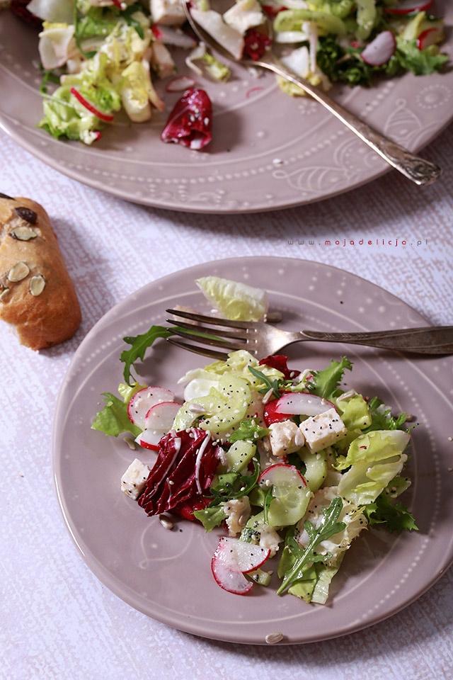 Sałatka z ogórkiem, rzodkiewką, białym serem typu włoskiego polana domowym miodowym winegretem. Do tego opcjonalny dodatek, czyli chrupiąca posypka z prażonych ziaren słonecznika, maku i sezamu, którą uwielbiamy.