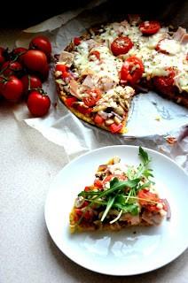 mam dla Was przepis na szybszy w wykonaniu i zdecydowanie zdrowszy odpowiednik pizzy wykonany na spodzie z pysznej kaszy jaglanej. Wszechstronność zastosowania tej kaszy jest nie do pobicia, jeśli jeszcze nie zagościła w Waszym menu, to po tym przepisie zmienicie zdanie :)    Lista składników na 1 pizzę (wystarczy dla 2-3 osób)  - szklanka kaszy jaglanej  - sól, pieprz, przyprawa do pizzy  - 3 łyżki przecieru pomidorowego  - ulubione dodatki (u mnie pieczarki, czerwona cebula, wędlina z kurczaka, pomidorki koktajlowe, tarty ser mozzarella, rukola)   Krok po kroku  1) Kaszę zalewamy dwoma szklankami wrzątku. Dodajemy łyżeczkę soli i gotujemy przez ok. 12 minut aż wsiąknie wodę. Zdejmujemy z ognia, dodajemy 2 szczypty pieprzu, pół łyżeczki przyprawy do pizzy i blendujemy na gładką masę.  2) Ciasto równo wykładamy na wyłożoną papierem blaszkę i dociskamy wyrównując brzegi. Pieczemy w nagrzanym do 180 stopni piekarniku przez 15 minut.  3) Spód smarujemy przecierem pomidorowym, wykładamy ulubione dodatki, posypujemy przyprawą do pizzy i tartym serem. Zapiekamy kolejne 10 minut.   Smacznego!
