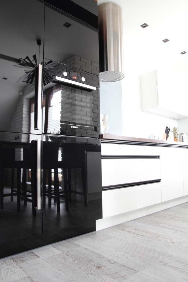Białe szafki kuchenne kontrastują  z ciemnym sprzętem AGD w nowoczesnej kuchni w jednym z apartamentów w Bydgoszczy. Szafki zostały wykonane na wymiar przez naszą firmę Mobiliani.