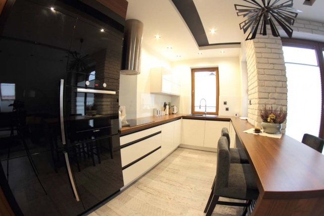 Podświetlony widok na wnętrze kuchni utrzymanej w jasnych barwach z szafkami i innymi meblami kuchennymi wykonanymi na wymiar przez Mobiliani dla klienta z Bydgoszczy.