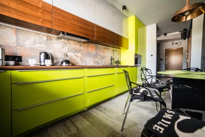 Oryginalne meble kuchenne w kolorze limonki, pochodzące z apartamentu Lake Resident w Bydgoszczy. Meble wyprodukowała firma Mobiliani, a projekt wnętrza architekci z pracowni JLT Design.
