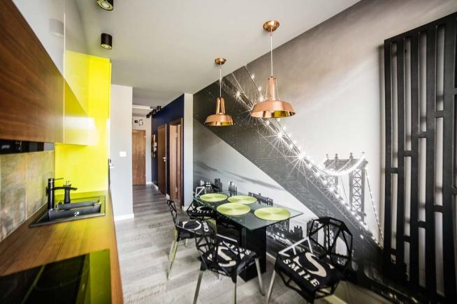 Wnętrze oryginalnej, limonkowo-żółto-czarnej kuchni z Bydgoszczy, z meblami kuchennymi od Mobiliani. Na środku znajduje się czarny stół z przezroczystym blatem.