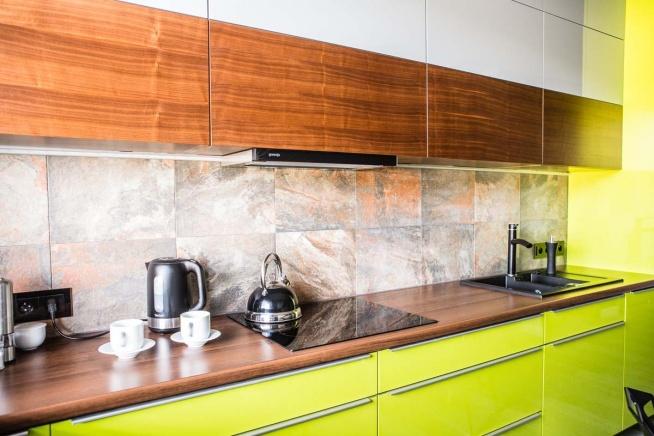 Zbliżenie na szafki i meble kuchenne w kolorze naturalnego drewna oraz limonki we wnętrzach jednego z apartamentów w Bydgoszczy. Meble zostały wyprodukowane przez firmę Mobiliani, producenta mebli na wymiar, projekt zaś wykonało studio projektowania wnętrz JLT Design.