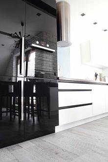Białe szafki kuchenne kontrastują  z ciemnym sprzętem AGD w nowoczesnej kuchn...