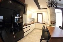 Podświetlony widok na wnętrze kuchni utrzymanej w jasnych barwach z szafkami ...