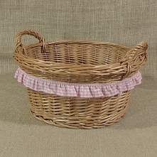 Okrągły wiklinowy koszyczek z uszkami, zdobiony wstążką z falbanką.
